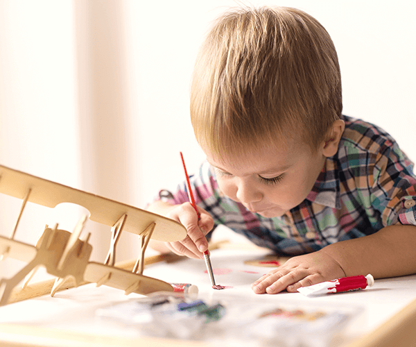 toddler painting with a model plane