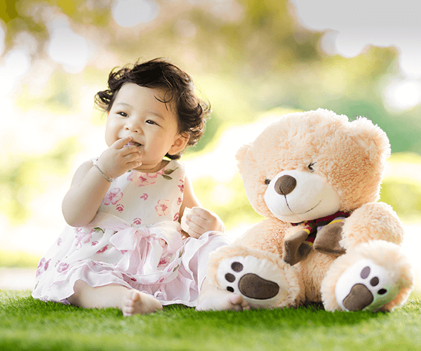 little girl sitting with a stuffed bear